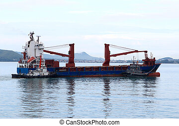 Tugboat assisting bulk cargo ship to harbor quayside