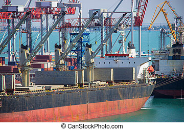 Tugboat assisting container cargo ship to harbor quayside.