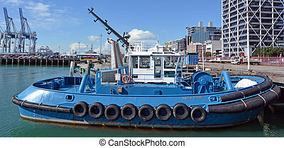 AUCKLAND, NZL - AUG 01 2015:Tugboat mooring at Captain Cook Wharf in Ports of Auckland, New Zealand. Tugboat, small, strongly built vessel, used to guide large oceangoing ships into and out of port