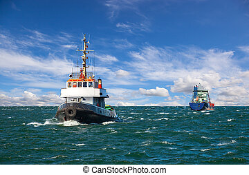 Tugboat and sea bulk carrier with pilot boats.