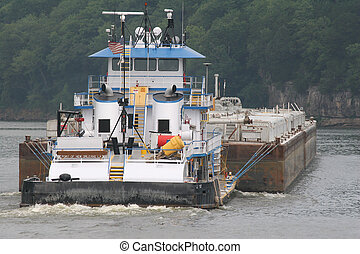 Tugboat pushing barge, misty morning on the river
