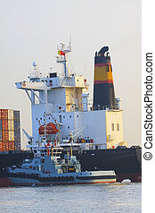 tugboat beside big container ship i