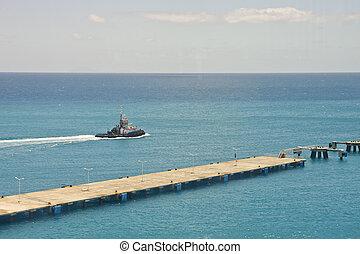 Tugboat Cruising Past Pier