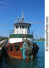 Tugboat in the clear blue Caribbean ocean docked in the port of Nassau, Bahamas