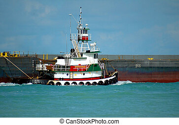 Photographed tugboat pulling barge in Florida inlet.