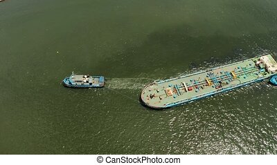 Tugboat pulling heavy loaded barge. - Aerial view of...