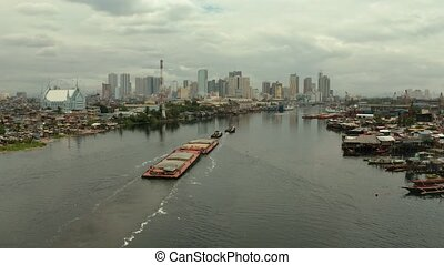 Tugs pulling heavy barge on the river top view. Tugs and cargo ship on the river.