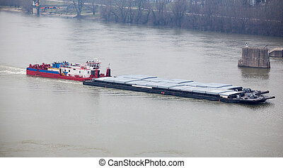 Tugboat Pushing a Heavy Barge - Top view of Tugboat pushing...