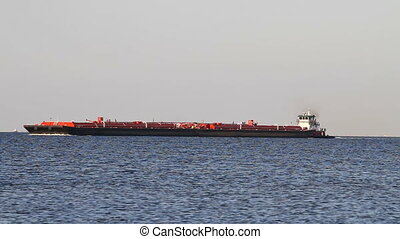 Tugboat Pushing Barge - Tugboat pushes a tanker barge along...