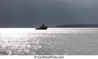 Tugboat sailing in the seaport waters in backlighting...