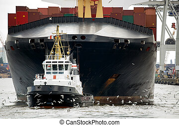tugboat towing freighter in harbor - tugboat towing...