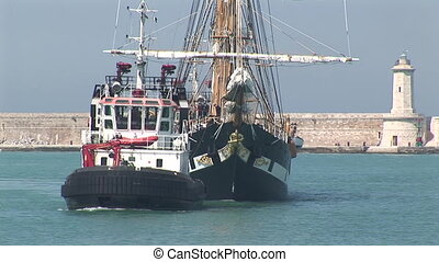 Tugboat towing sailing vessel