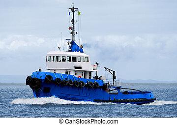 Tugboat underway at sea in calm waters.