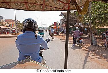 tuk tuk driver in a busy street