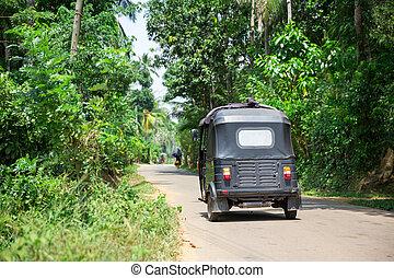 Tuk tuk on road of Sri Lanka, back view. Ceylon tropical...