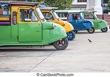 Tuk tuks lined up in a side ally in Bangkok