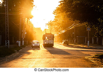 TULA, RUSSIA - JUNE 6, 2013: Car and tram on traffic light stop under golden sun backlight. Air glowing bright.