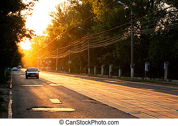 TULA, RUSSIA - JUNE 6, 2013: Car on city street under golden sun backlight. Air glowing bright.