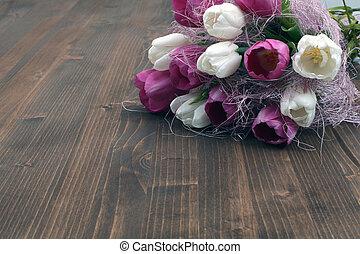 Tulip bouquet on wooden board.