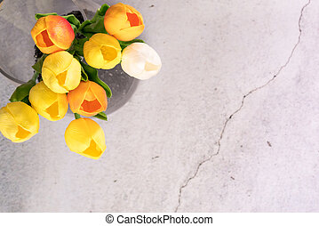 tulip flower in the glass jar with crack white cement background spring concept