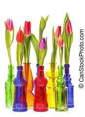 tulip flowers in colorful glass vases