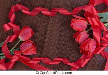 tulip on wooden background with red ribbon