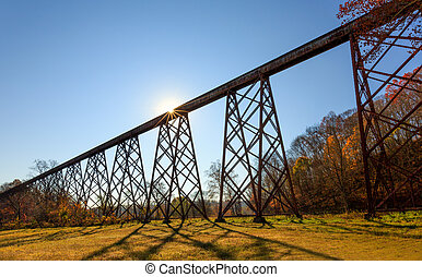 The morning sun silhouettes the Tulip Trestle, also know as the Greene County Viaduct, one of the world's longest train trestles.