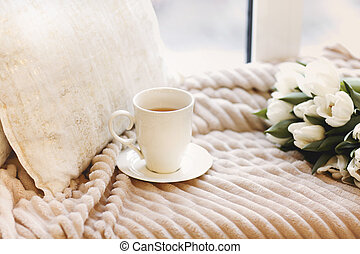 Tulips and cup of coffee on bed