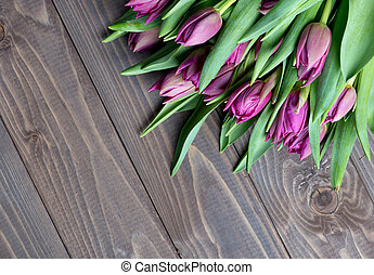 tulips bouquet on wooden background.