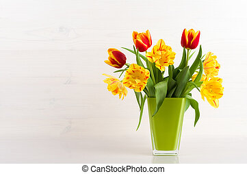 Tulips in a vase on a white wooden background