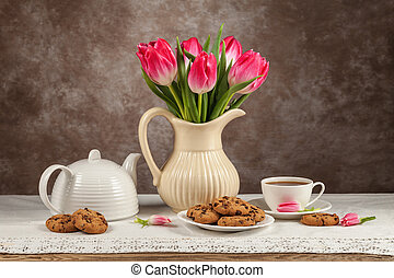 Tulips in a vase, tea, chocolates on the board
