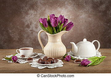 Tulips in a vase, tea, chocolates on the board.