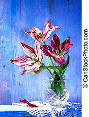 tulips in vase on wood background