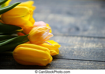tulips in wooden background. Easter card. With space for your greetings