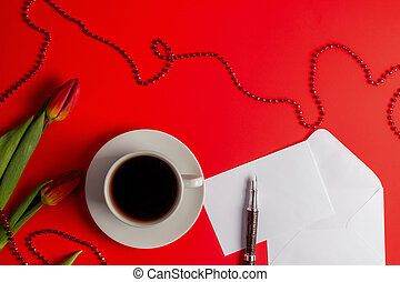 Tulips, white envelop with card, pen and cup of coffee on red background. Flat lay, top view.