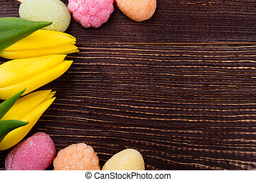Tulips with sweets on wood.