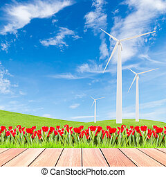 tulips with wind turbine on green grass field against blue sky background and wood plank foreground,used for green earth concept
