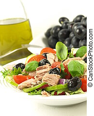 Tuna salad with black olives, tomatoes and grapes in a background