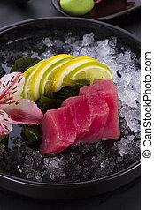 Tuna sashimi with ice on a black plate