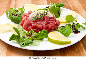 tuna tartare with fresh salad and lemon slice