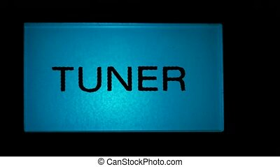 Tuner button blue color on black background of radio...