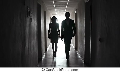 Tunnel Vision - Man and woman passing by the room doors of...