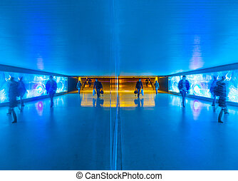 tunnel with pedestrians in motion in blue cool light