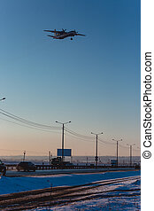 Turboprop aircraft landing, flying over the highway.
