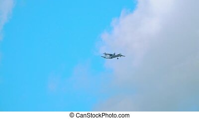 Turboprop airplane flying in the sky. Slow motion telephoto...