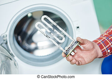 Washing machine repair. Hand of repairer with turbular electric heating element