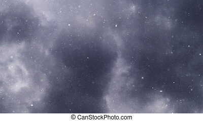 Turbulent snowfall from dark gray clouds as winter season...