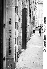 Tuscany, Italy. An art gallery signseen in a street full of turism.