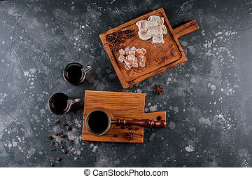 Turk and a glass of coffee on a wooden board, dark background. Top view.