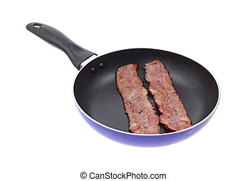 Turkey bacon in skillet - Two pieces of turkey bacon cooking...